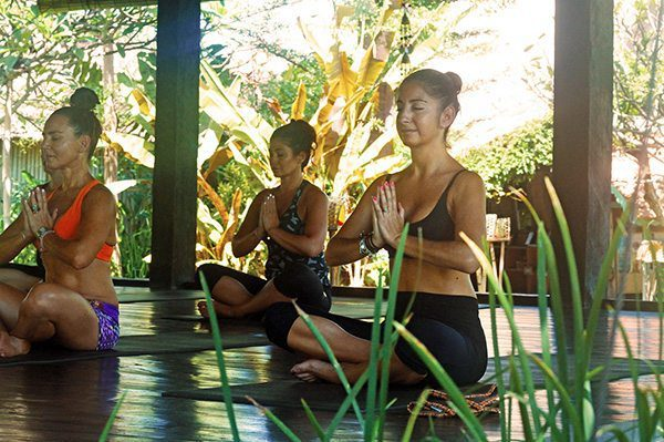 Women performing yoga in beautiful yoga shala. Yoga for all levels at our Bliss Yoga Retreats in Bali