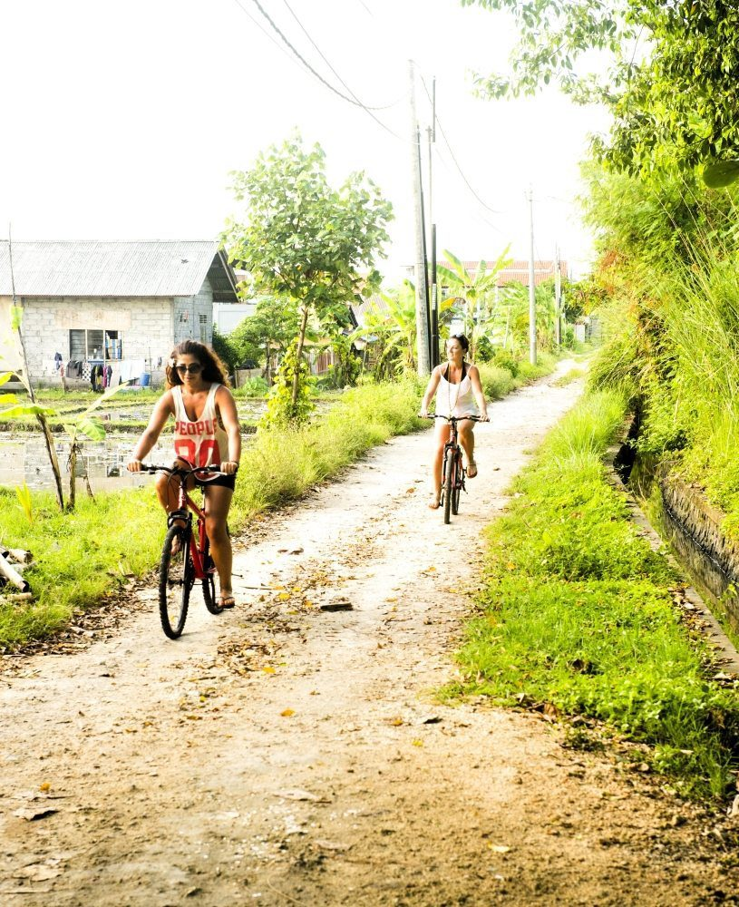 Women riding bicycles in Bali - Thrill seeker package Eco Bike Tour through rice fields experiencing the real Bali a little slower