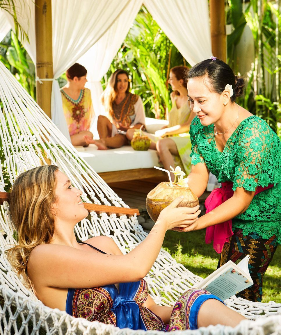 Relax and unwind, lady in hammock sipping coconut at our Bali Retreat Centre