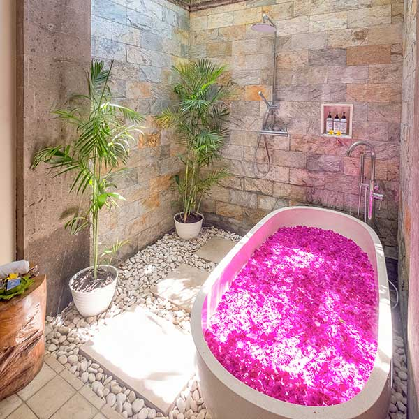 Gorgeous luxury outdoor bathroom with stone wall and rose petal bath in Bali retreat, Bliss Retreat Room, Bliss Sanctuary For Women, Canggu