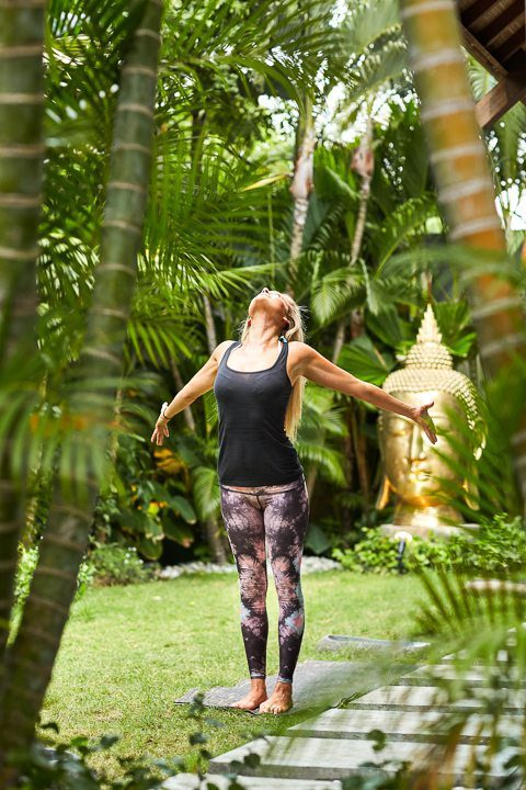 Woman doing yoga stretch in beautiful garden at Bali yoga and spa retreat Bliss Sanctuary For Women