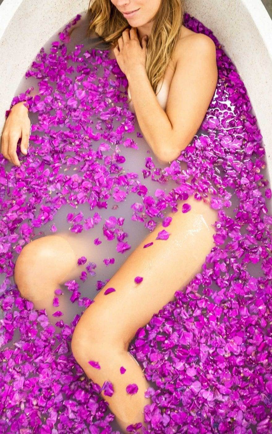 Woman relaxing in flower bath at Bali wellness retreat