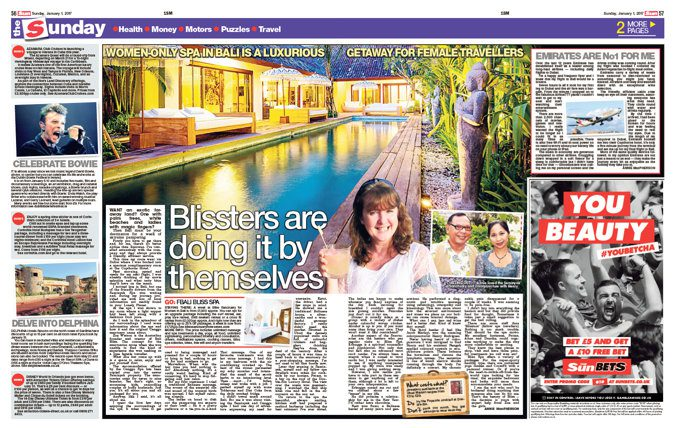 newspaper clipping - woman holding cocktail next to a long rectangular pool at a luxury Bali villa during twilight