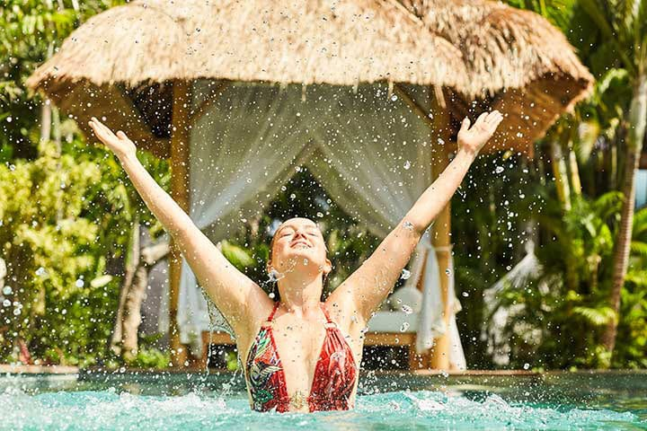 Bliss Sanctuary girl in pool happy with arms outstretched